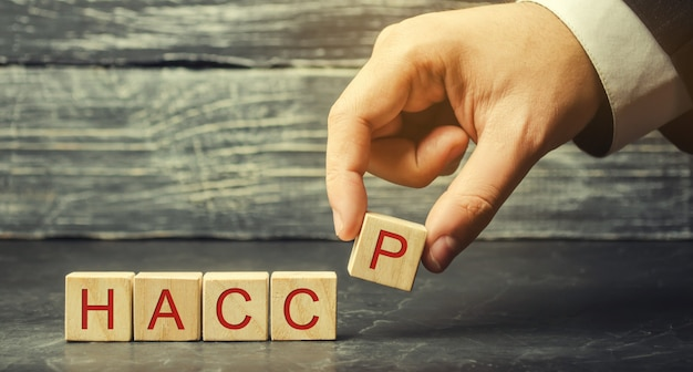 A man puts wooden blocks with the word haccp.
