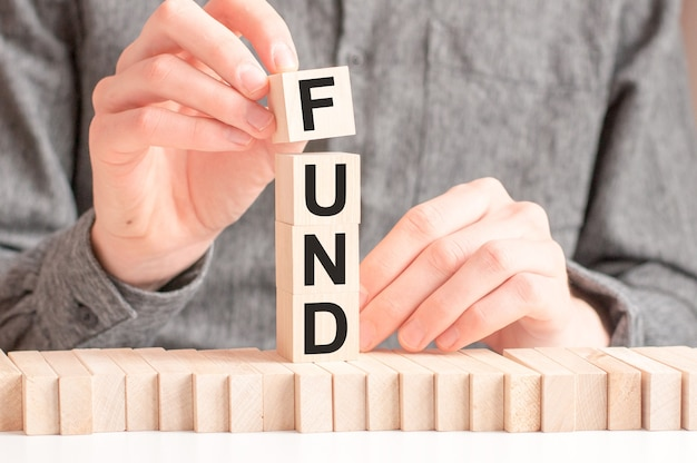 남자는 fund라는 단어에서 문자 f로 나무 큐브를 넣습니다.
