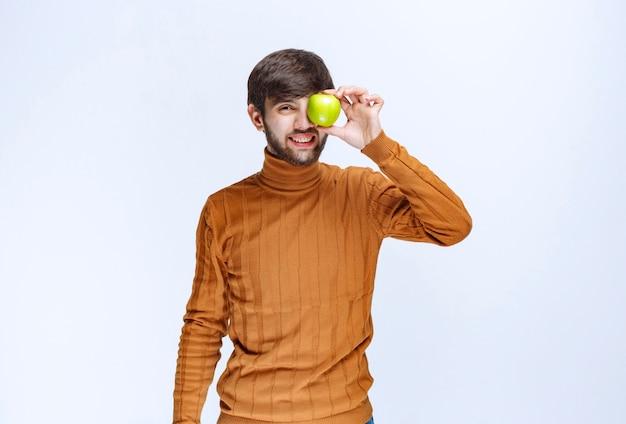 Человек прикладывает зеленое яблоко к глазу.