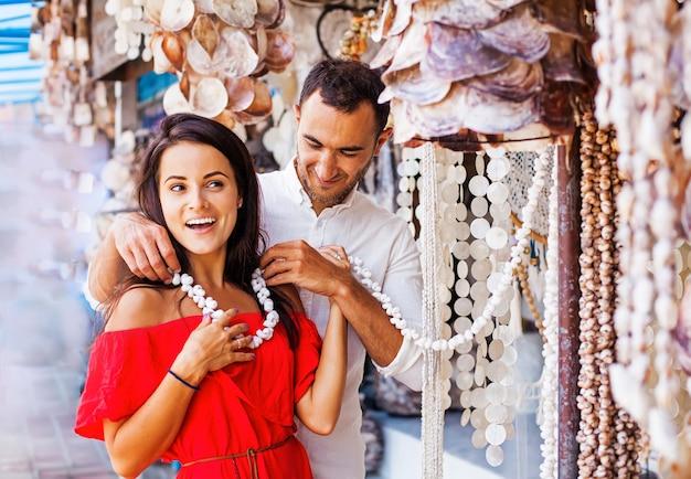 伝統的な市場で女性に貝殻のネックレスを置く男性