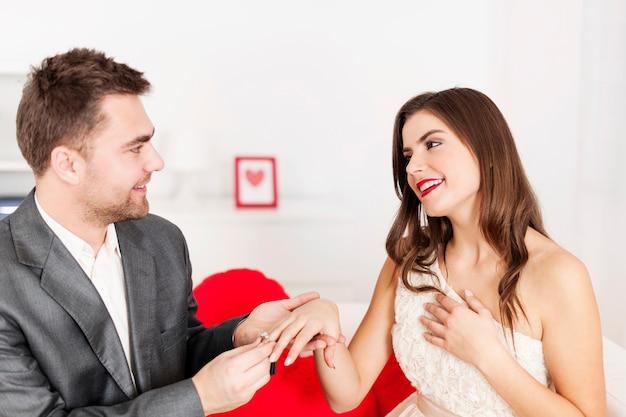 그의 여자 친구의 손가락에 결혼 반지를 씌우는 남자