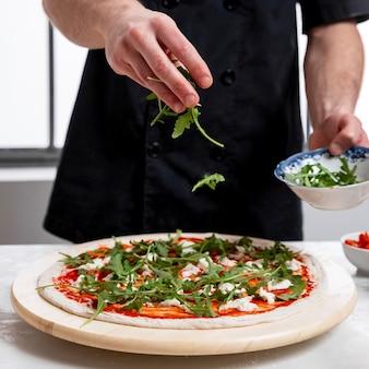 Человек кладет рукколу на тесто для пиццы