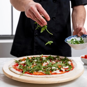 Man putting arugula on pizza dough