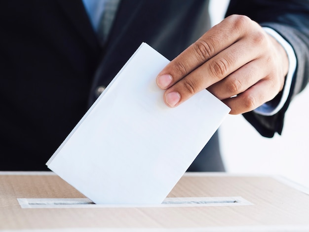 Man putting the ballot in a box close-up