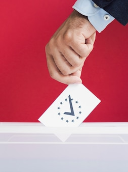 Man putting a ballot in a box with red background