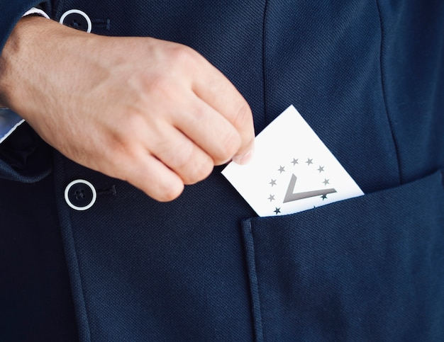 Man putting a ballot in his pocket