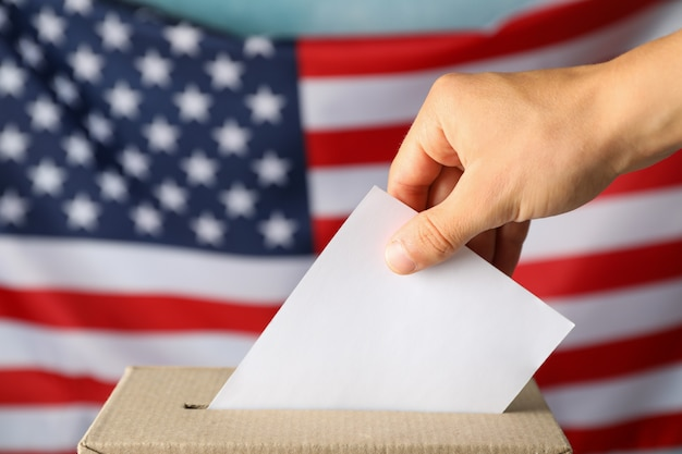 Man putting ballot into voting box against american flag