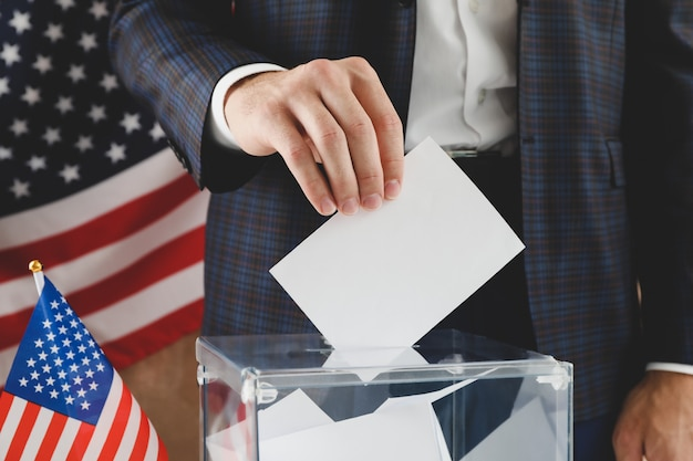 Man putting ballot into voting box against brown surface with american flag
