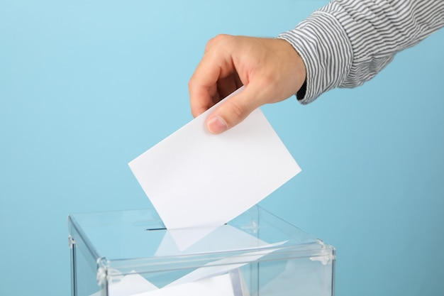 Человек кладет бюллетень в урну для голосования