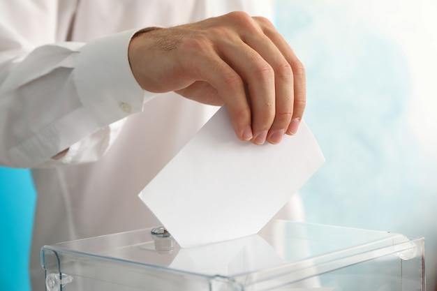 Man putting ballot into voting box