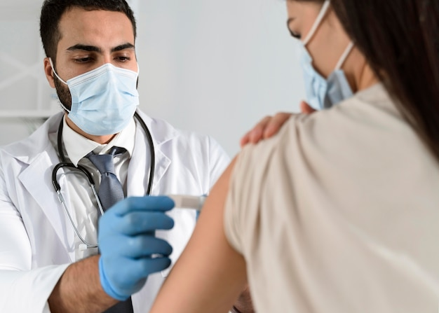 Man putting a bandage on a patient's arm