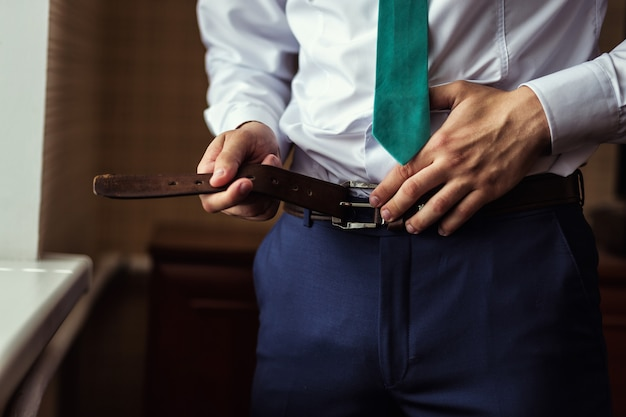Man putting on a belt, businessman, politician, man's style, male hands closeup, american businessman, european businessman, a businessman from asia, people, business, fashion and clothing concept