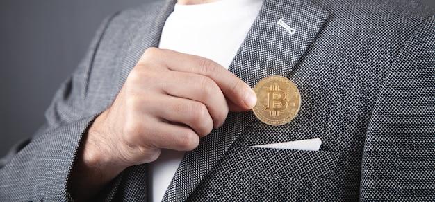 ビットコインをスーツのポケットに入れている男。