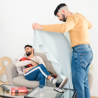 Man putting blanket over his boyfriend sleeping with baby on sofa at home