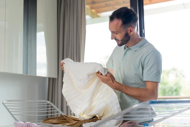 Uomo che mette i vestiti nell'asciugatrice in casa