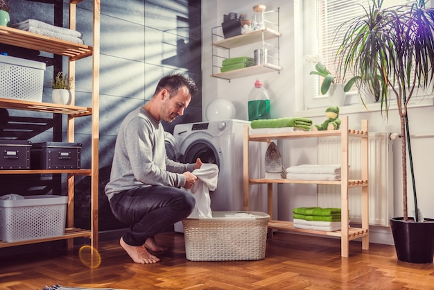 Man putting clothes into washing machine