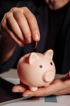 ピンクの貯金箱のクローズアップにコインを入れている男。お金の節約の概念