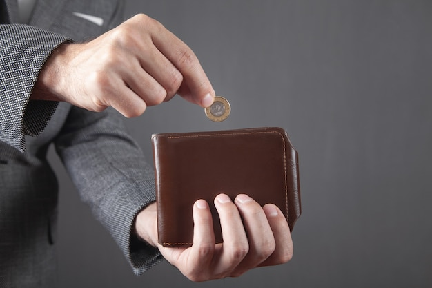 財布にコインを入れる男。