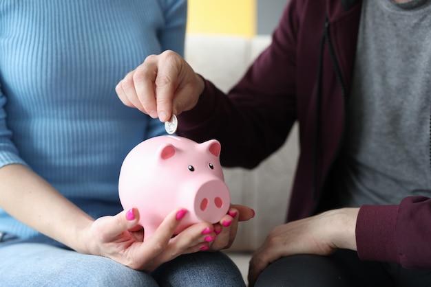 그의 아내 근접 촬영의 손에 분홍색 돼지 저금통에 동전을 넣어 남자