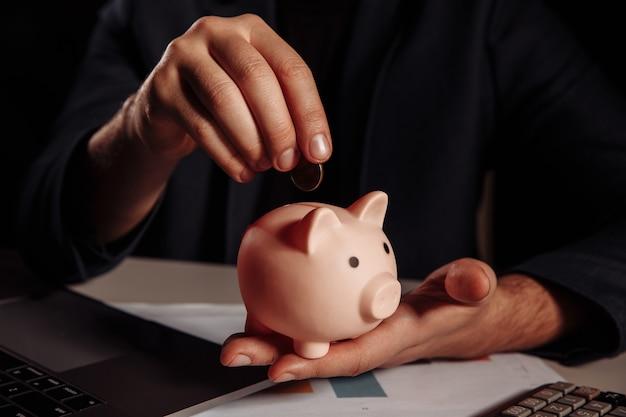 Man putting coin in pink piggy bank close-up. savings concept.