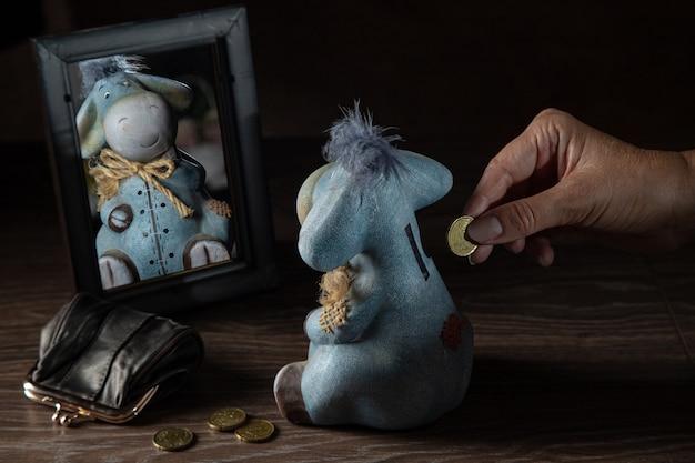 돈 상자에 동전을 넣는 남자. 거울에 비친 당나귀 모양의 저금통, 동전이 든 지갑, 퇴직금