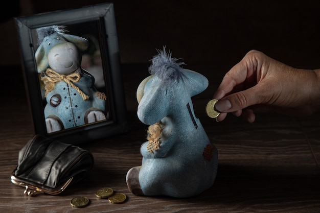 Man putting coins into money box. donkey shaped piggy bank reflected in the mirror, wallet with coins, retirement financial