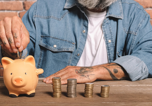 Man putting coins into piggy bank with stack of coins on table to save money and financial concept