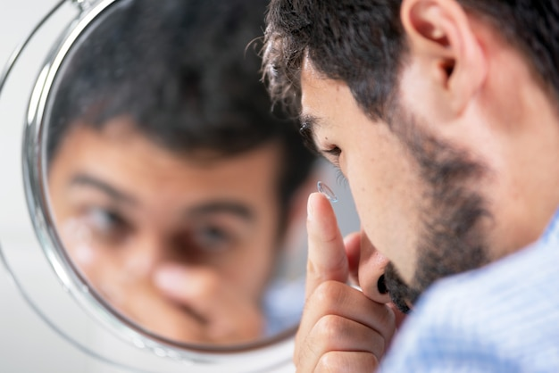 Man putting on contact lens in ophthalmology clinic.