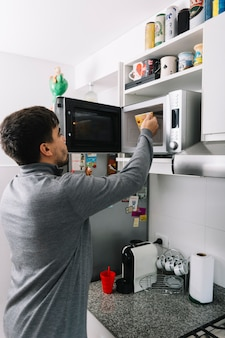 Man putting cup inside microwave oven