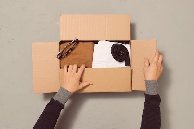 Человек кладет различную одежду в коробку карбона. концепция пожертвования или повторного использования одежды