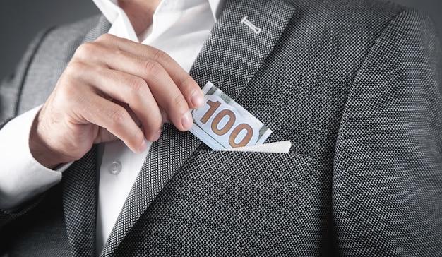 スーツのポケットにドル紙幣を入れる男。
