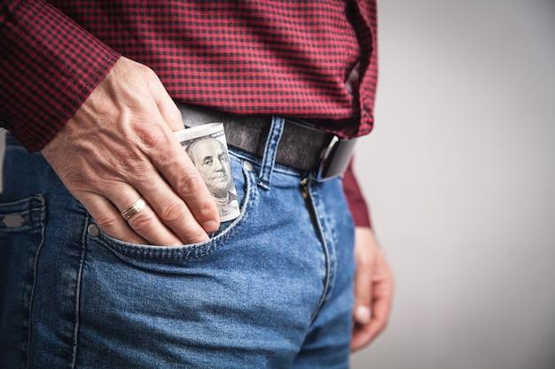 Человек кладет доллары в карман.