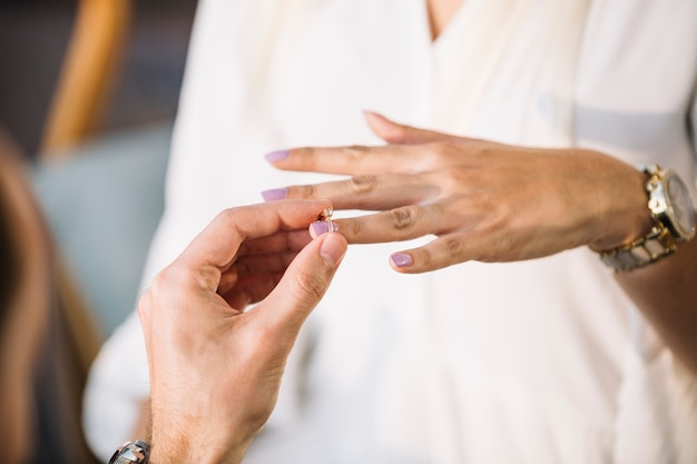 Man putting engagement ring on his fiancee's finger