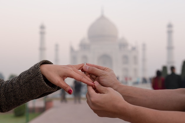 Man putting on engagement ring on his wife finger with taj mahal in background.
