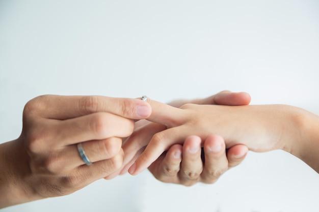 男は、女性の手に婚約指輪を置きます