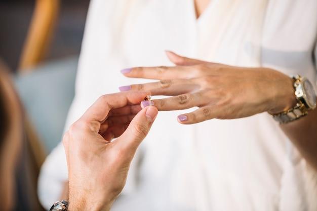 그의 약혼녀의 손가락에 약혼 반지를 퍼 팅하는 남자