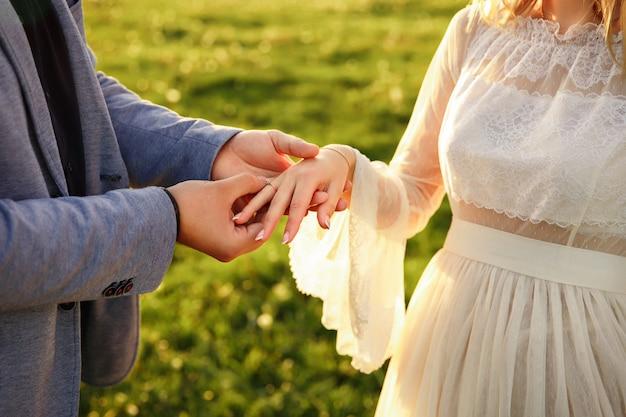 Мужчина ставит обручальное кольцо на руке женщины. брак, свадьба