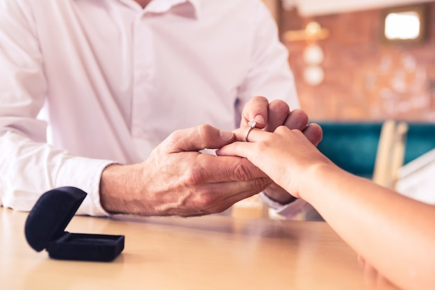 女性の指に婚約指輪を置く男