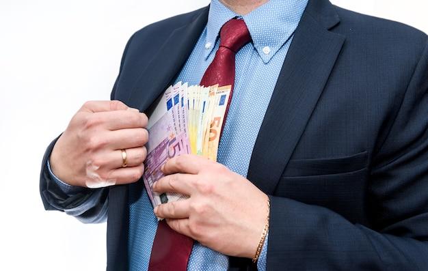 Человек кладет банкноты евро в карман куртки