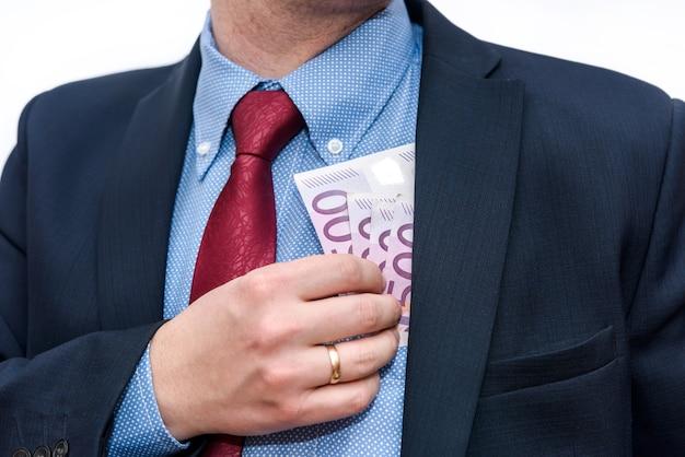 ジャケットのポケットにユーロ紙幣を置く男