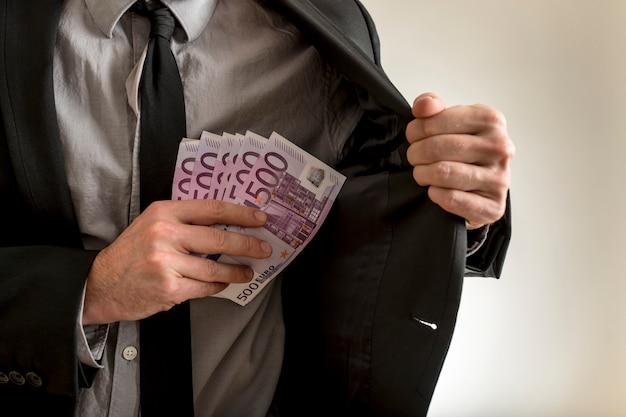 Man putting euros inside his jacket pocket