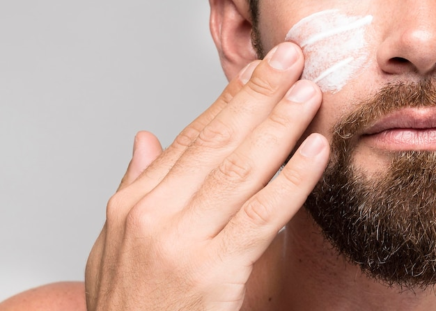 Man putting on face cream close-up