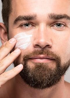 Uomo che mette sulla crema per il viso