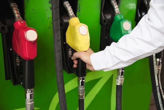 Мужчина заправляет бензином топливо в машину на заправочной станции