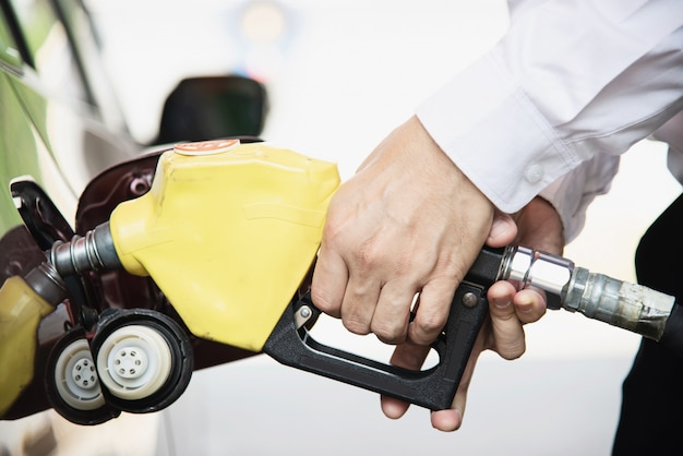 Man putting gasoline fuel into his car in a pump gas station