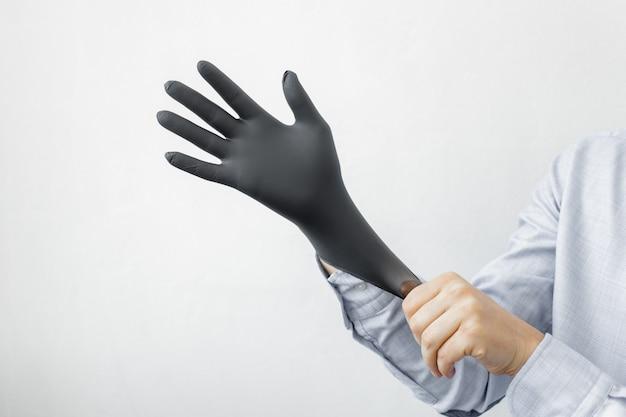 男は彼の手に手袋を置きます。