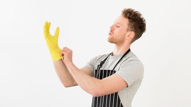 Человек надевает перчатки для чистки