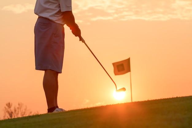 Человек кладет мяч для гольфа на закат