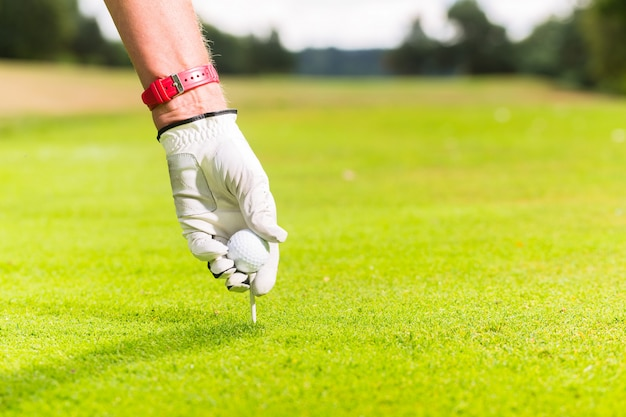 Man putting golf ball on tee, close shot