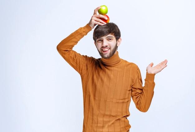 Человек кладет зеленое яблоко на голову.